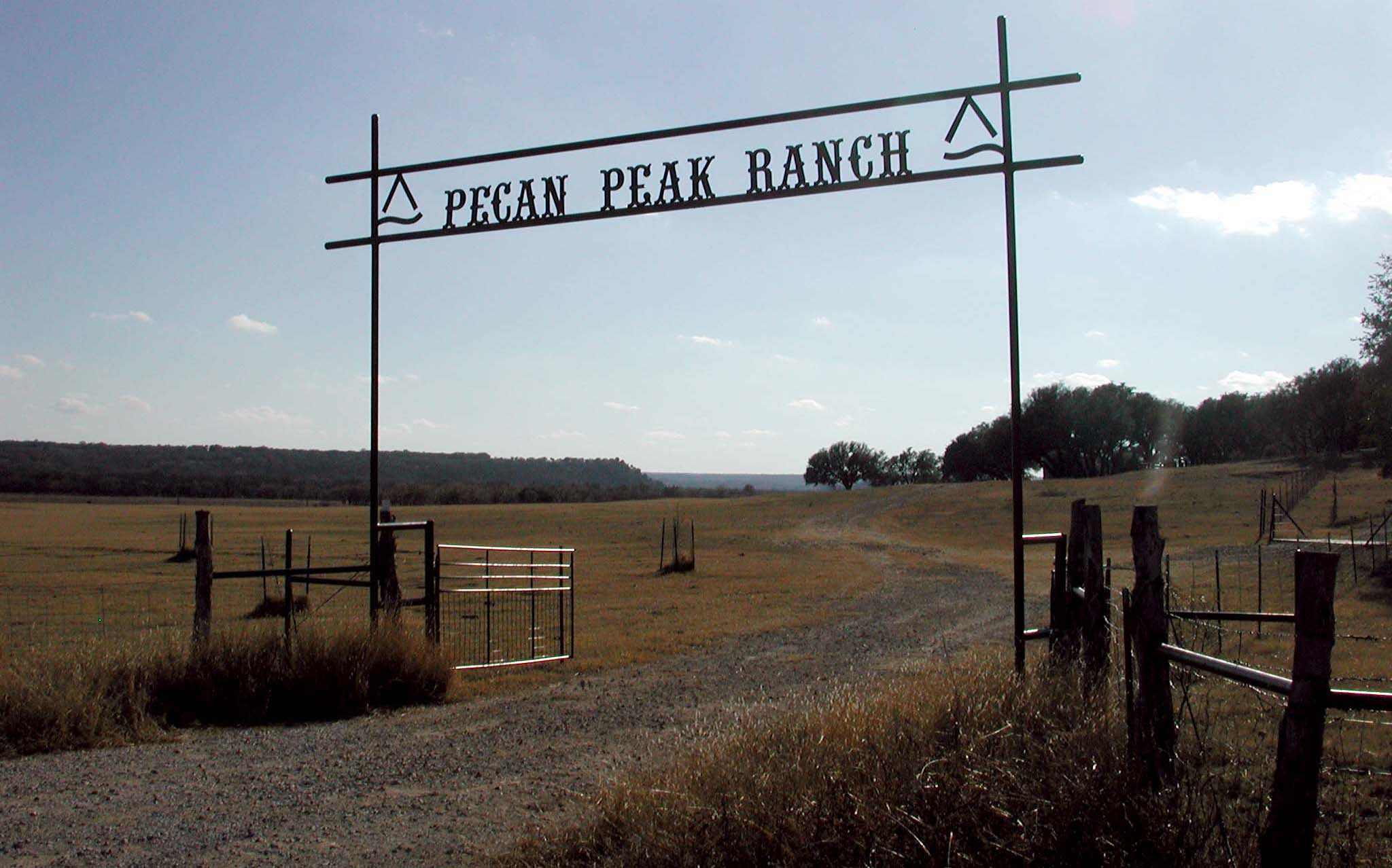 Metal sign over the front gate at Pecan Peak Ranch with Red Peak in the background.